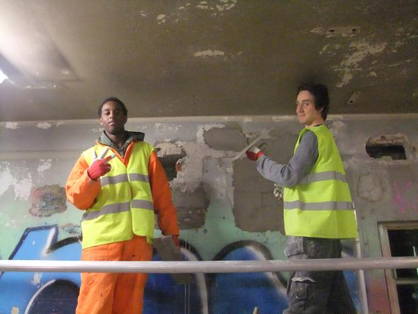 Kaksi nuorta kunnostamassa rakennusta työhaalarit päällään